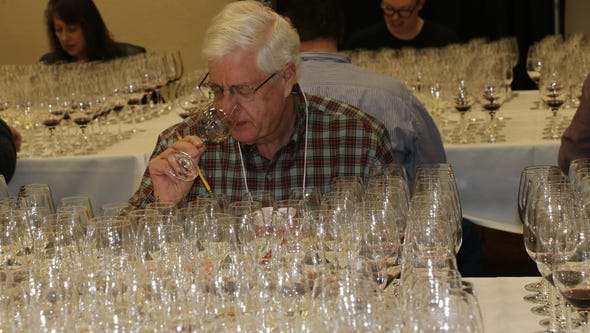 A judge checks a glass of wine at the competition.