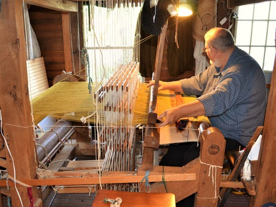 Bill Leinbach displays a few of the items that he weaves