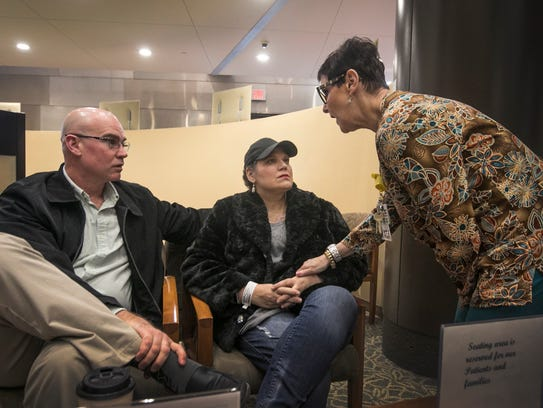 Jason Newton, left, of Handy Township waits in lobby of Karmanos Cancer Institute with his wife, Kimberlie Newton, 45, as Karmanos medical assistant Iris Burman retrieves Newton for her appointment Monday, March 12, 2018.