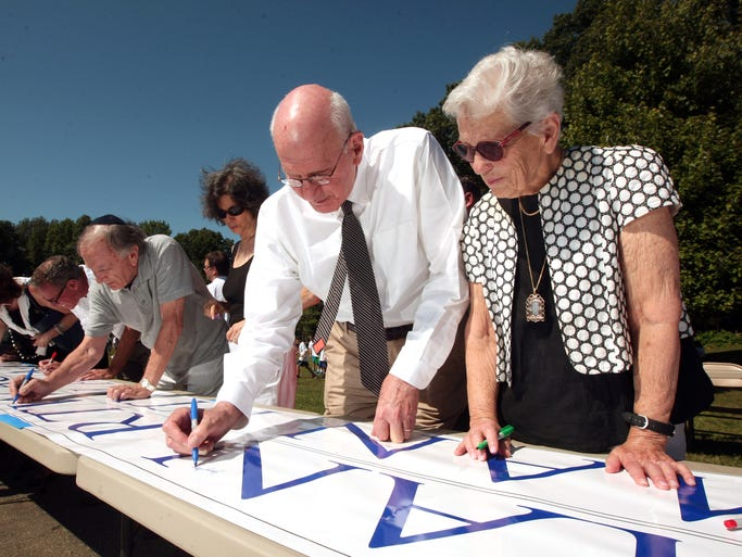 Leading benefactors Jerry and Paula Gottesman sign a banner as the Hebrew Academy of Morris County is being renamed Gottesman RTW Academy, in recognition of a $15 million challenge gift from the Gottesman's of Morris Twp, and in tribute to the schoolâ??s founding families: Rubenstein, Turner, and Wertheimer. September 4, 2014, Randolph, NJ. Photo by Bob Karp