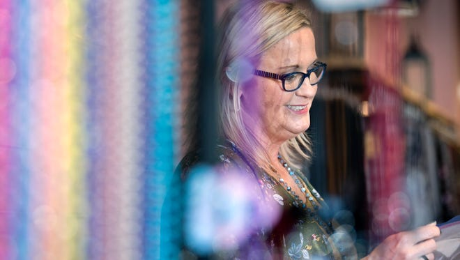 From behind rows of beaded necklaces, Rhonda Moubray, of Milan, admires pearl earrings Wednesday, Oct. 25, 2017, at The Corner Boutique's new location at 1319A Union University Dr. in Jackson. Moubray opened The Corner Boutique in Milan four years ago with her business and life partner, Jeff Newbill. The ladies clothing and accessory store is open 10 a.m. to 6 p.m. Monday through Friday and 10 a.m. to 5 p.m. Saturday in Jackson.