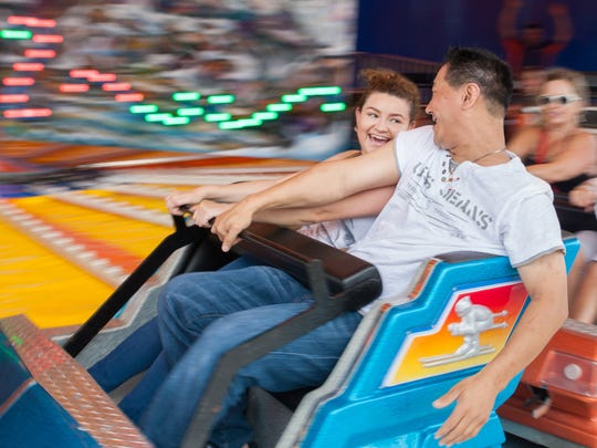 Dinora Canales and Anthony Bernalt, of Cape Coral, hang on as they ride the Music Express at the Collier County Fair in on Sunday, March 20, 2016.
