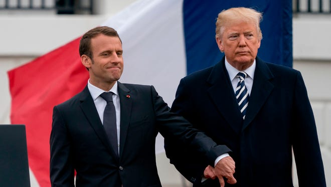 This April 24, 2018 file photo shows President Trump and French President Emmanuel Macron hold hands during a State Arrival Ceremony on the South Lawn of the White House in Washington, D.C.