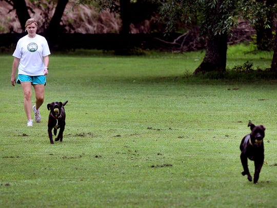 Molly Jennings walks with her dogs Ruby and Janet at Bark Springs in Smyrna in this 2016 photo.