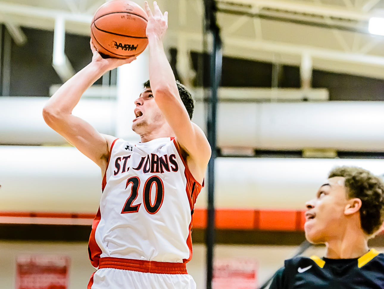 Ross Feldpausch ,20, of St. Johns pulls up to hit a short jump shot during a game last month against Waverly. Feldpausch helped the Redwings wrap up CAAC Red play unbeaten Friday with a win over Mason.