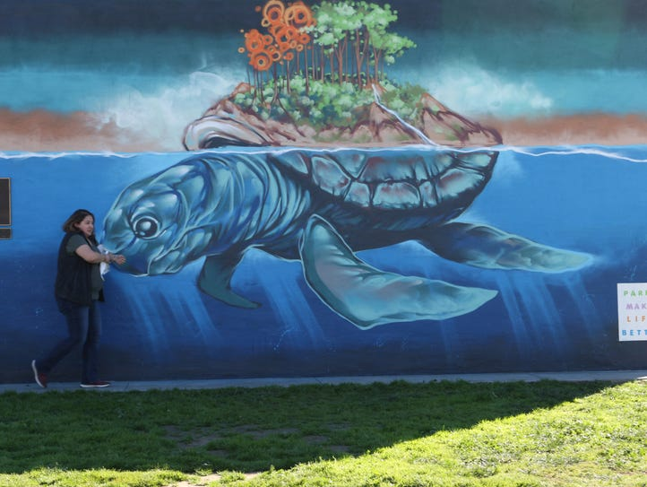 Jacky Luna walks in front of the new mural at La Paz