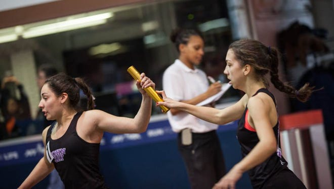 John Jay's Pippa Nuttall hands off the baton to Carmela Culhane during the Section 1 Kickoff 2 meet at The Armory in Manhattan on Sunday, December 11th, 2016.