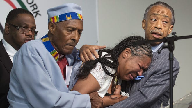 Esaw Garner, wife of Eric Garner, breaks down in the arms of Rev. Herbert Daughtry, center, and Rev. Al Sharpton, right, during a rally at the National Action Network headquarters for Eric Garner, Saturday, July 19, 2014, in New York.  Garner, 43, died Thursday, during an arrest in Staten Island, which a plainclothes police officer placed him in what appeared be a choke hold while several others brought him to the ground and struggled to place him in handcuffs.