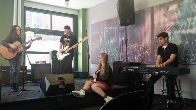 From left: Riley Kirkpatrick (aka Kcold Pizza) and funky folky rock musician Sydney Burnham jam together during a video shoot at the Detroit Institute of Music Education to promote The Warehouse Rocks in Livingston County.