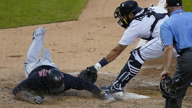 Cleveland Indian' Carlos Santana beats the throw to Detroit Tigers catcher Austin Romine to score during the fourth inning of a baseball game, Friday, Aug. 14, 2020, in Detroit.