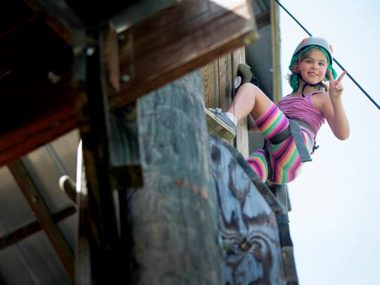 Allie Broering, 8, of Kentucky, looks down from atop