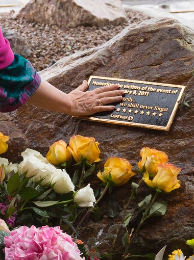 Tucson resident Valerie Miller touches a memorial plaque outside the Safeway grocery store where the Tucson shootings occurred five years ago on Jan. 8, 2011.
