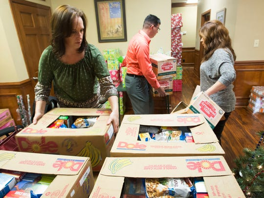 Samantha Barrett, left, Time Chandler, center, and Dianna Montoya, from Panhandle Warrior Partnership, work to finish food boxes for in need military veterans just in time for the holidays.