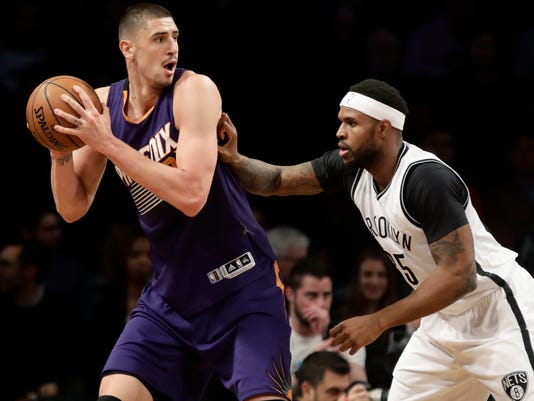 Phoenix Suns' Alex Len, left, is defended by Brooklyn Nets' Trevor Booker (35) during the first half of an NBA basketball game Thursday, March 23, 2017, in New York. (AP Photo/Frank Franklin II)