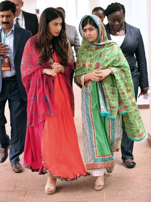 Pakistani education activist Malala Yousafzai listens to Malala Fund committee member Shiza Shahid as she arrives at the State House in Abuja to meet the Nigerian president.