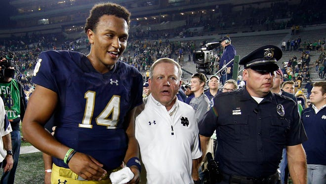 Oct 29, 2016; South Bend, IN, USA; Notre Dame Fighting Irish coach Brian Kelly walks off the field with Notre Dame Fighting Irish quarterback DeShone Kizer (14) at Notre Dame Stadium. Notre Dame defeats Miami 30-27. Mandatory Credit: Brian Spurlock-USA TODAY Sports