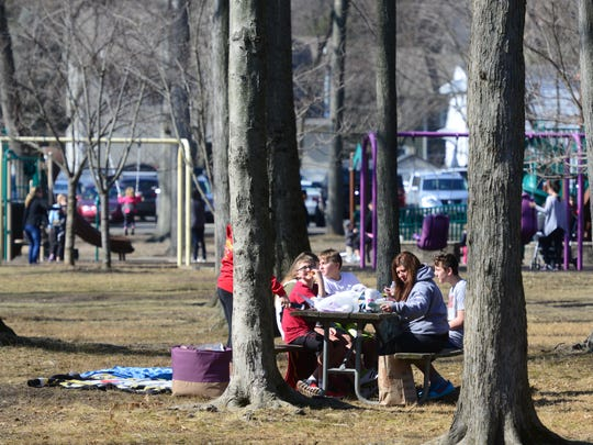 The Martorano family and the Theriault family enjoy their lunch at the Saddle River County Park Wild Duck Pond Area Thursday in Ridgewood. The unusual warm February afternoon brought crowds to the parks and sidewalks for lunch Thursday afternoon in Ridgewood.