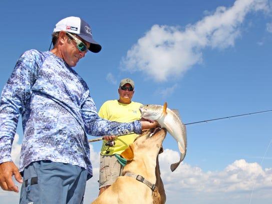 Capt. Scott McCune with his trademark canine deckhands,
