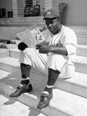 Montreal Royals player Jackie Robinson looks over a