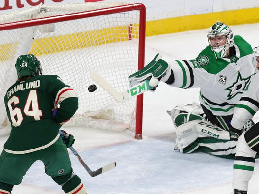 Dallas Stars goalie Kari Lehtonen (32) deflects a puck in front of Minnesota Wild right wing Mikael Granlund (64) during the third period of an NHL hockey game Thursday, March 29, 2018, in St. Paul, Minn. The Wild defeated the Stars 5-2. (AP Photo/Andy Clayton-King)