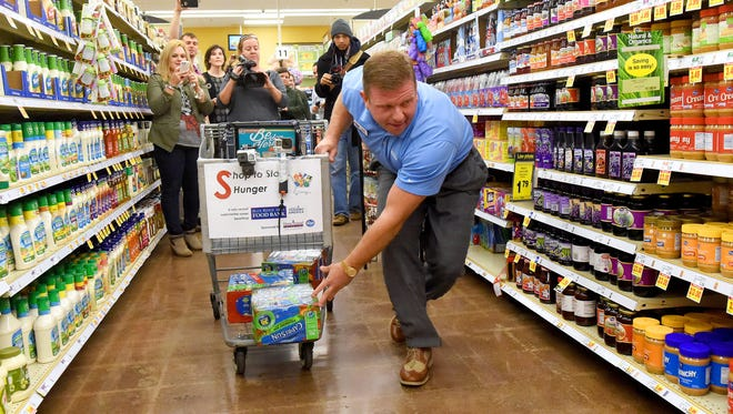 Scott Simons of Valley Auto Group tosses groceries in and under his cart as he goes. He races against 60 seconds as he tries to get as many items in his shopping cart as he can. Local celebrities raced against the clock and each other for Shop to Stop Hunger event held to benefit the Blue Ridge Area Food Bank at Kroger in Staunton on Thursday, Dec. 15, 2016. Simons walked away with the Cart Away Hunger Hero Award from the event.