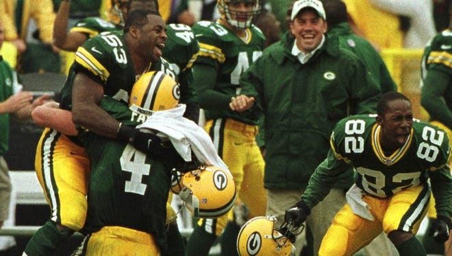 Brett Favre is embraced by George Koonce (53) after winning the game in the final seconds. At right is Desmond Howard.