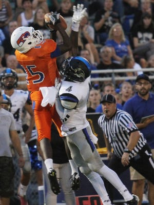 Cape Coral's Chris Lewis makes the first down despite Ida Baker's Willie Overstreet during Friday night's game.