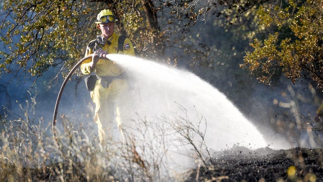 A firefighter helps to extinguish a 3-acre vegetation fire that burned Tuesday evening off Coyote Lane in Happy Valley.