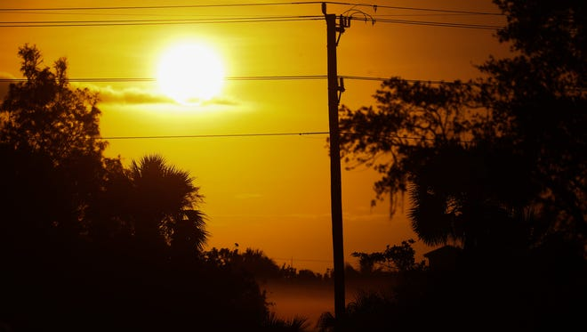 The sun rises over utility poles and North Fort Myers on Tuesday. Many in the area are still without power after Hurricane Irma raked the area.