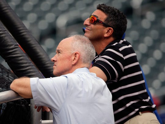 New York Mets general manager Sandy Alderson, left, and his special assistant, J.P. Ricciardi, watch batting practice before a game between the Colorado Rockies and the Mets, in 2015.