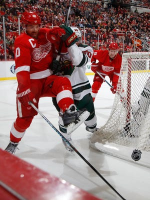 Red Wings forward Henrik Zetterberg fights his way by the Minnesota Wild Ryan Suter in the third period of the Wings shoot out win in their hockey game on Tuesday, Jan.20, 2015 in Detroit.