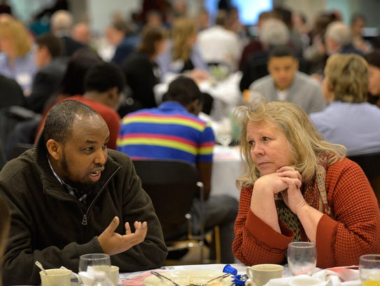 Catholic Charities employees Ismail Mohamed, left,