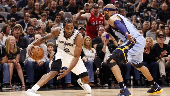 San Antonio Spurs small forward Kawhi Leonard (2) dribbles the ball as Memphis Grizzlies shooting guard Vince Carter (right) defends during the second half in game two of the first round of the 2017 NBA Playoffs at AT&T Center.