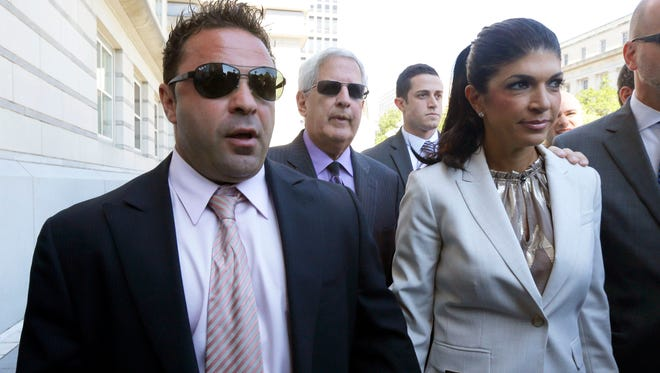 "In this July 30, 2013 file photo, ""The Real Housewives of New Jersey"" stars Giuseppe ""Joe"" Giudice and his wife, Teresa Giudice of Montville Township, N.J., walk out of Martin Luther King, Jr. Courthouse after an appearance in Newark. Teresa served 11 months in prison and Joe began his 41-month sentence on Wednesday."