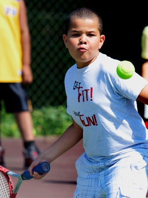 J.C. Quintana, 8, of York City, eyes a return during the first day of the Tennis for Kids program at Farquhar Park on Monday, June 22, 2015.