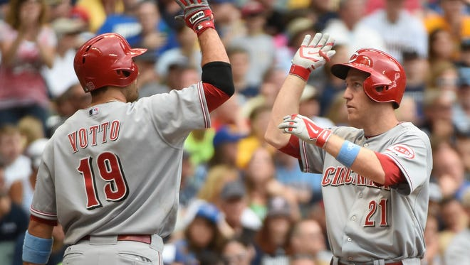Reds third baseman Todd Frazier is greeted by first baseman Joey Votto after hitting a two-run homer in the fifth inning Sunday against the Milwaukee Brewers at Miller Park.
