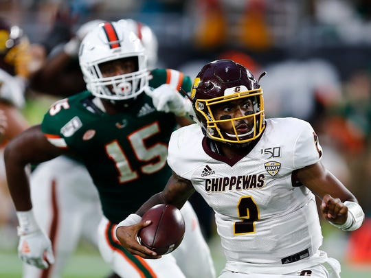 Central Michigan quarterback David Moore (2) runs with the ball against Miami defensive lineman Gregory Rousseau (15) during the second half of an NCAA college football game, Saturday, Sept. 21, 2019, in Miami Gardens, Fla. (AP Photo/Brynn Anderson)