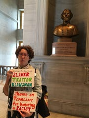 A woman protests the bust of Nathan Bedford Forrest