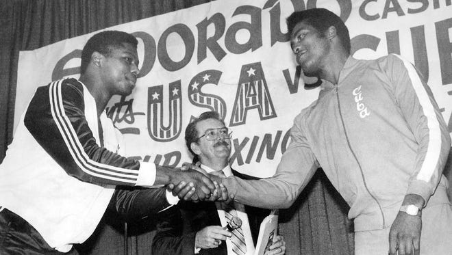Olympic gold medal heavyweight boxers Tyrell Biggs of the United States and Teofilo Stevenson of Cuba shake hands before they met in a USA-Cuba bout in Reno in February 1984. The US Olympic Boxing Trials are being held in Reno in December.