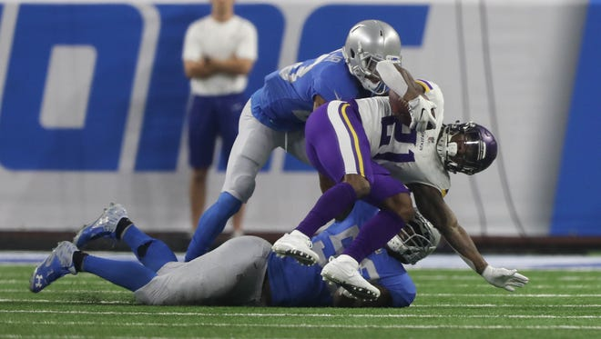 Lions defenders tackle Vikings RB Jerick McKinnon during the first quarter on Thursday, Nov. 23, 2017, at Ford Field.