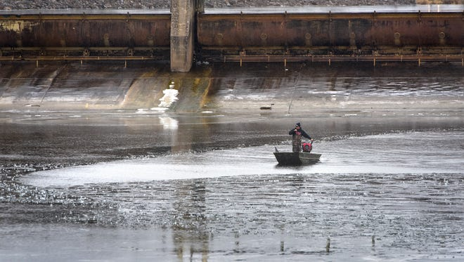 A fisherman uses a boat to travel near a patch of thin ice under the Sartell Dam Friday, Nov. 24, in Sartell.