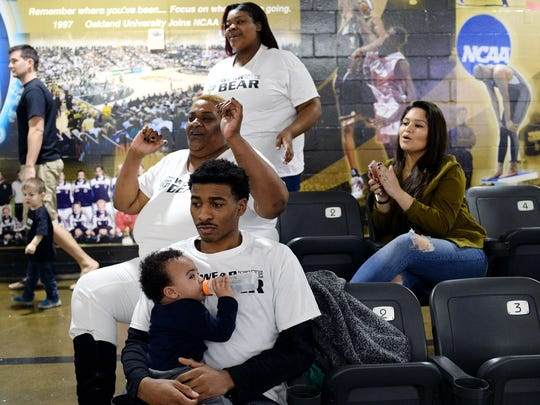 (From back left) Kironia Walker, 15, her mother, Laurel, and Indira Garcia, Sherron Dorsey-Walker's girlfriend, cheer for Sherron Dorsey-Walker as Carlos Walker, 19, holds his nephew, Chaz, 1, all of Detroit, during the Oakland-UIC game on Feb. 19, in Rochester.