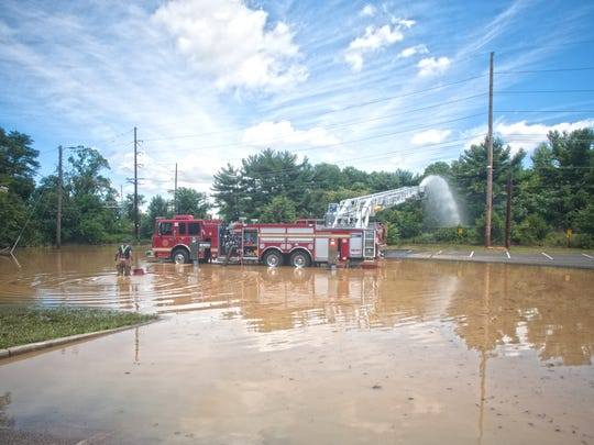 Glassboro Fire Department works on flood clean-up in a parking lot area after heavy rain flooded Triad Apartments complex at Rowan University in Glassboro