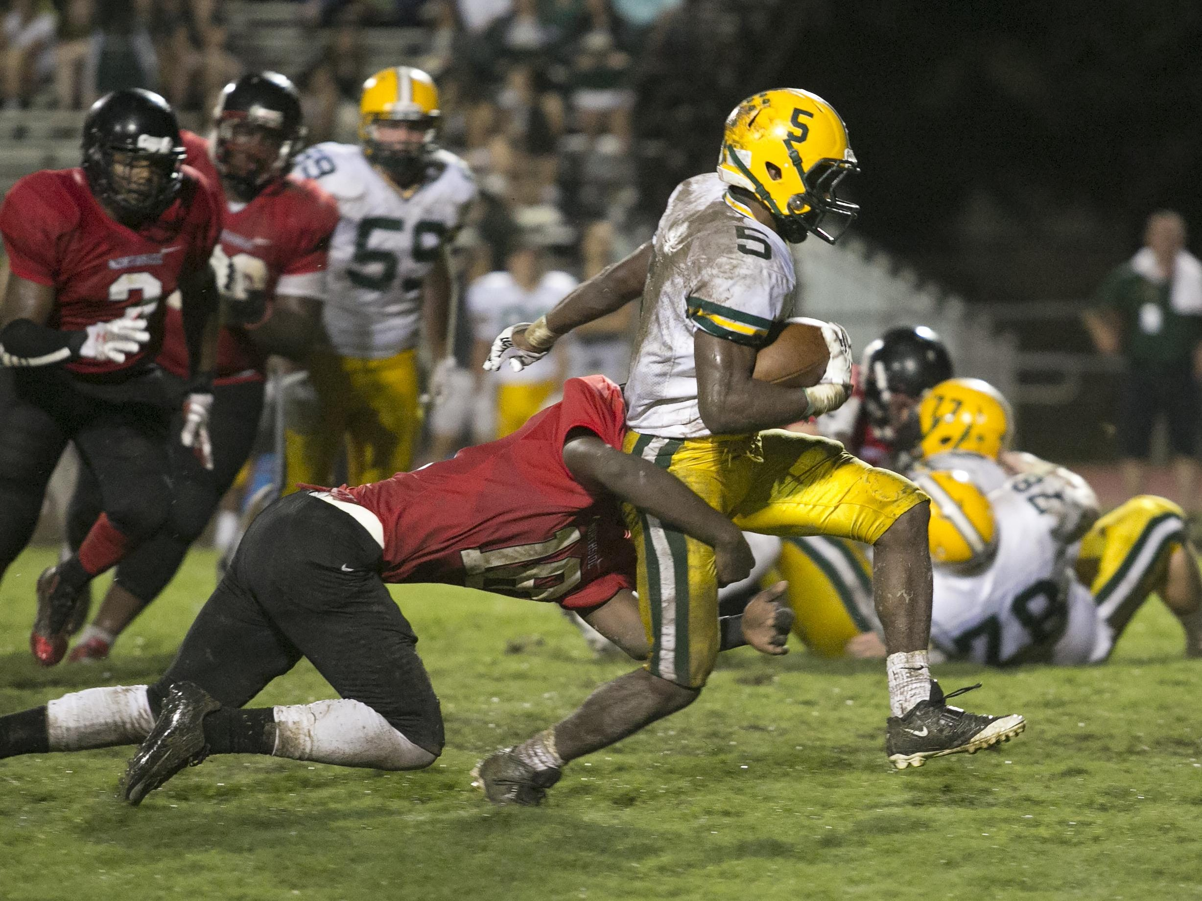 Cecilia's Raymond Calais breaks tackles to gain extra yardage during the Bulldogs' win over Northside.