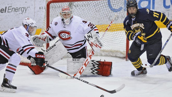 St. Cloud State's Nate Widman (left) and Quinnipiac's Tim Clifton (11) chase after a loose puck in front of Huskies goalie Charlie Lindgren last season at the Herb Brooks National Hockey Center in St. Cloud.