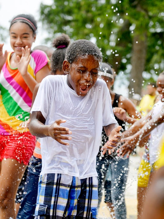 Marquez Sutherland, 8 of York, plays with others in a new splash pad at Penn Park on Wednesday, July 15, 2015, before a dedication ceremony. Years-long efforts to update the park, which is the city's largest and oldest green space, have culminated in two new playscapes and a splash pad.