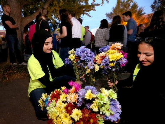 Sarah Alzabet, left, and Haneen Ahmad separate flowers to pass out during the Murfreesboro Muslim youth gathering to promote peace and unity Nov. 18, 2016, on the Square in Murfreesboro.