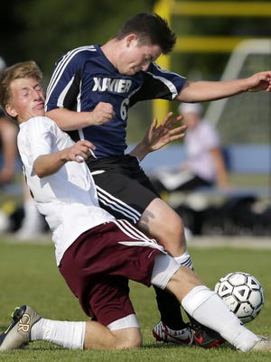 Fox Valley Lutheran's Colton Maxwell (left) collides with Xavier's Dan Kellberg on Thursday.