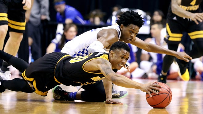 Northern Kentucky Norse guard Lavone Holland II (30) and Kentucky Wildcats guard De'Aaron Fox (0) scramble for possession of the ball during the second half of the first round of the NCAA Men's Basketball Championship in Indianapolis on Friday March 17, 2017. NKU lost 79-70.