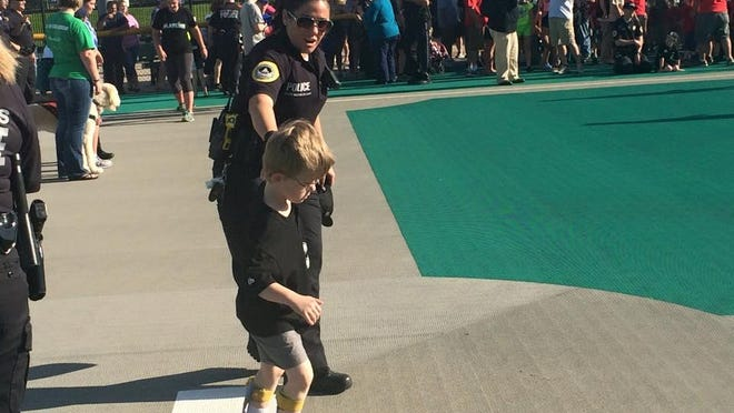 Jonathan Cluff, 5, of Des Moines runs around the bases with Des Moines Senior Police Officer Brookelyn Budd at the Miracle League Field, 529 S.W. Fifth St. in Des Moines, on Tuesday evening.